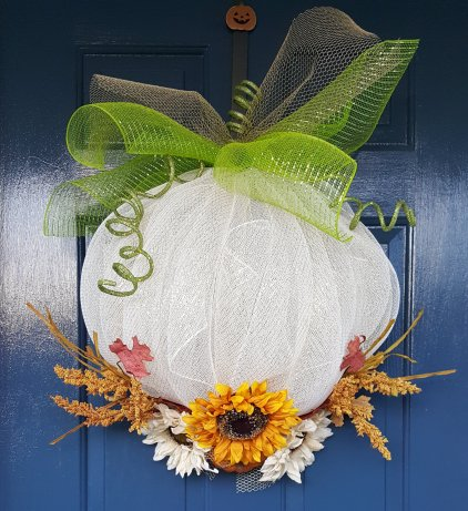 "Cinderella's Pumpkin 26"" Cream with gold foil deco mesh wreath. Embellished with seasonal florals, green glitter cord vines and stem, and gold mesh and green mesh for leaves. Price: $80"